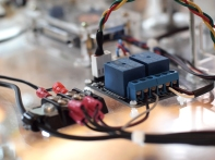 An Arduino brain sends a 5V signal to a 2 relay switches to toggle on/off power to the LEDs and stepper motor driver.
